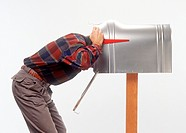 man leaning over with head in oversized mailbox