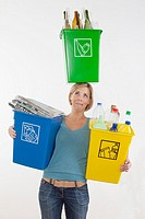 Woman balancing recycle bin on her head