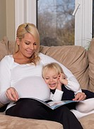 Happy pregnant mother and her three year old daughter reading a book together at home