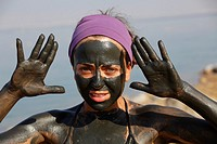 Young girl doing black mud therapy on the dead sea, Jordan