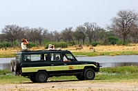 Touristen im Geländewagen bei der Tierbeobachtung am Khwai Fluss im Moremi Nationalpark, Botswana / Tourists in an off_road vehicle watching animals a...