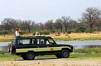 Touristen im Geländewagen bei der Tierbeobachtung am Khwai Fluss im Moremi Nationalpark, Botswana / Tourists in an off_road vehicle watching animals a...