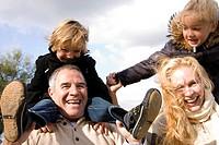 Happy parents carrying children on shoulders