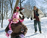 Father and daughters running in snow