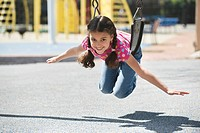 Hispanic girl swinging on playground swing