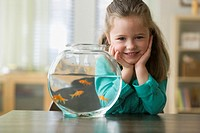 Caucasian girl standing next to fish bowl