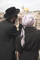 Middle East, Israel, Jerusalem, Orthodox Jewish couple gazing out over railing down to plaza and Western Wall, with Dome of the Rock in the distance. ...