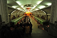 North Korea, Pyongyang. High angle view of commuters walking at the railroad station platform with two trains at the station