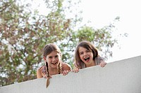 Grinning girls looking over wall