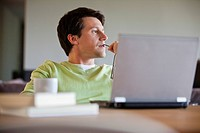 Man sitting with laptop and thinking