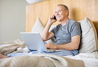 Man sitting in bed using laptop and cell phone