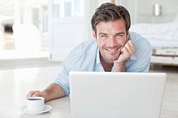 Man laying on floor with laptop and coffee