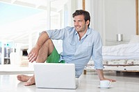 Man sitting on floor with laptop and coffee