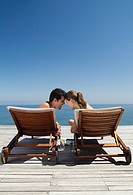 Couple sitting in lounge chairs near ocean