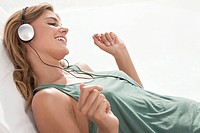 Woman reclining and listening to mp3 player