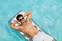 Man floating in swimming pool sunbathing