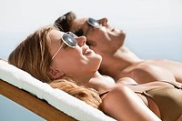 Couple laying on lounge chairs sunbathing
