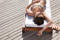 Teenager laying on lounge chair sunbathing