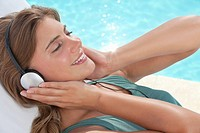 Woman listening to mp3 player near swimming pool