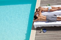 Couple laying on lounge chairs sunbathing near swimming pool