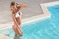 Woman in bikini standing in swimming pool