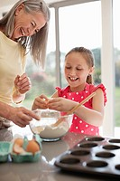 Grandmother and granddaughter baking cupcakes (thumbnail)