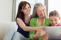 Grandmother, mother and daughter using digital tablet