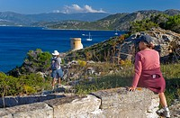 France, Corsica. Vistors above remains of Genoese tower on Point Mortella Punta Mortella on coast of Gulf of St. Florent Golfe de St. Florent. MR