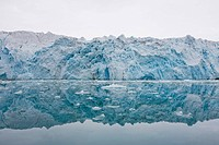 Norway, Svalbard, Spitsbergen, Ice face of Lilliehook Glacier reflected in calm water in Lilliehookfjorden in Krossfjorden on summer morning