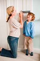 Mother measuring her son against a door with a book (thumbnail)