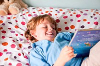Young boy reading a book on his bed (thumbnail)