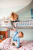 Young boys playfighting on their bunk bed