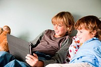 Two young boys on a bed, using a digital tablet (thumbnail)