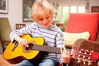 Young boy playing a guitar at home