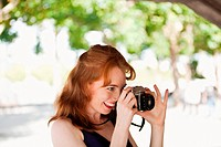 Young woman taking a photograph outside