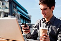 Young man working outside using his laptop and phone