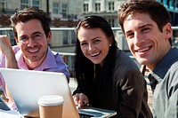 Three people smiling at the camera while using a laptop