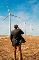 Man standing in front of wind turbines on mobile phone