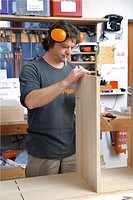 Germany, Upper Bavaria, Schaeftlarn, Carpenter fixing wood (thumbnail)