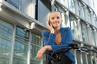 Germany, Bavaria, Teenage girl with cell phone on bicycle, smiling, portrait