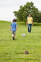 Germany, Bavaria, Father and son playing soccer in park