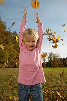 Germany, Bavaria, Girl playing with leaves, smiling