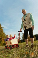Germany, Bavaria, Grandfather pulling granddaughters sitting in wagon