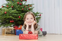 Germany, Munich, Girl with present near christmas tree
