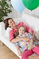 Germany, Munich, Mother and daughter with balloon on couch, smiling