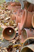 Terracotta flowerpots stored under garden seat, Uk, November