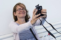 Greece, Ionian Islands, Ithaca, Mid adult woman photographing herself, smiling