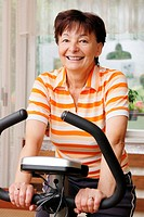 Mature woman exercise on spinning bicycle at home