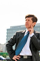 Portrait of thinking senior business man looking away with building in background