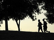 silhouette lonely runners in woods at dusk